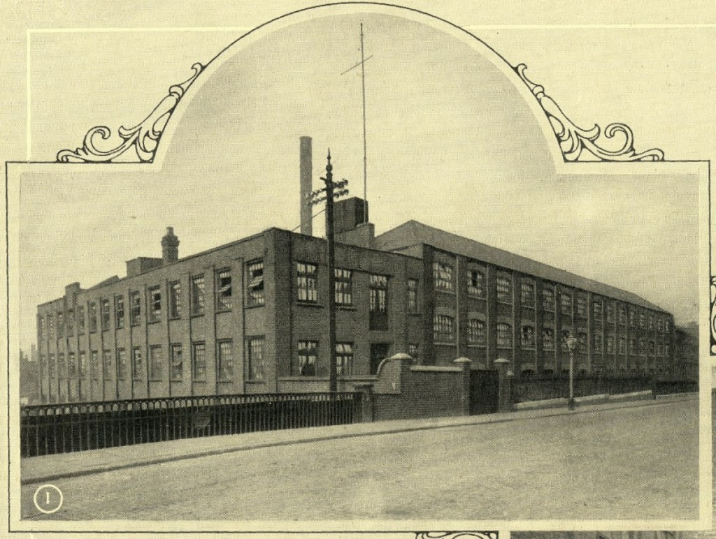Large factory on several floors, next to canal bridge with decorative iron railings