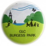 Circular badge with graphic showing lake, trees and church, with kids and pram, and text 'GLC Burgess Park'.