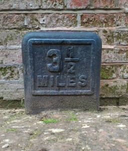 Cast-iron milepost set in canal towpath against a brick wall