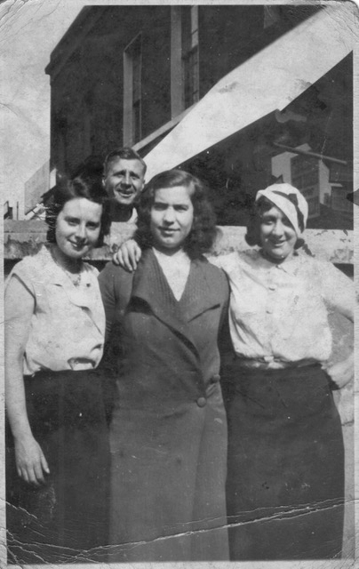 3 women standing in front of a wall, with a man peering over behind them. A shop awning and sign are visible beyond