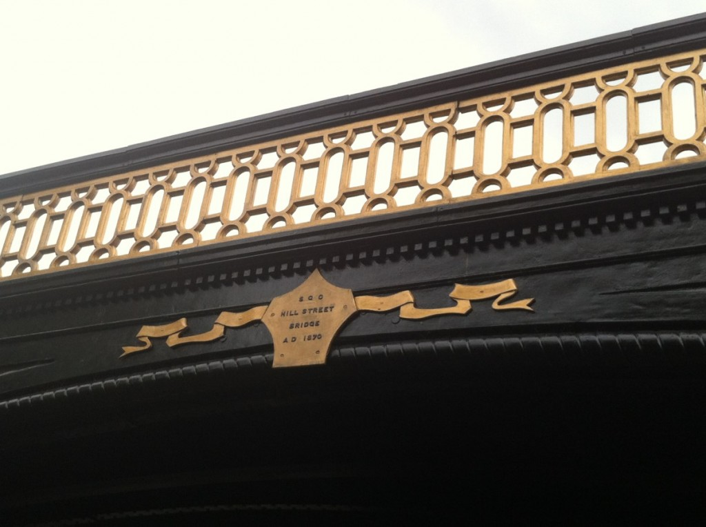 Gold painted plaque with black lettering spelling out S.G.C Hill Street Bridge A.D. 1870