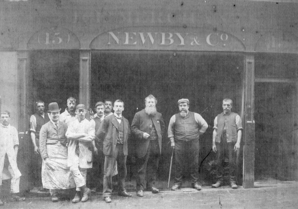 Black and white image of 11 men in the open front of the Newby and Co offices