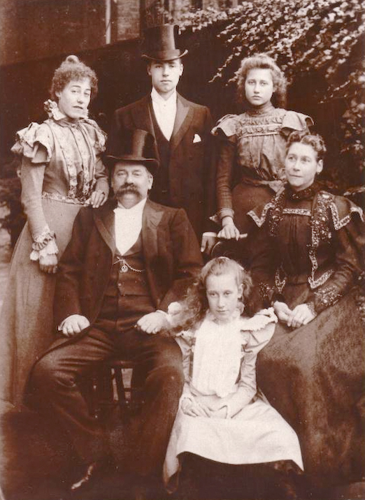 Sepia image of gentleman in top hat and tails and lady seated, with young daughter between.two young ladies and gent in top hat stand behind.