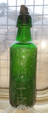 Green glass bottle with moulded lettering