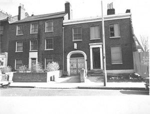B/W image of two former victorian house frontages with arched double dooorway in one