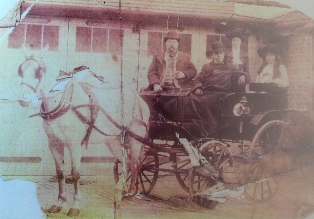 2 Edwardian gents and 2 ladies seated ona 4-wheel carriage with single white horse