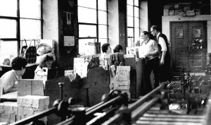 Women working at desks, 2 men chatting, machinery in forground