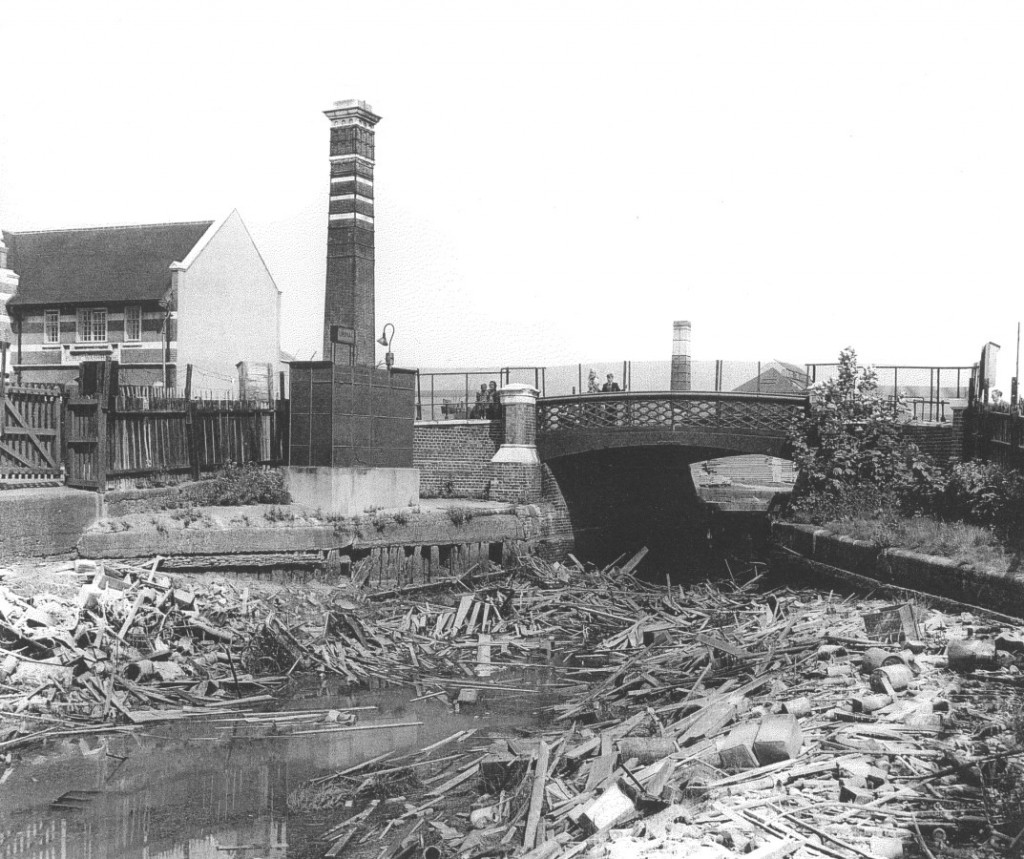 Old Library Baths and Washhouse building on the left, with Wells Way bridge over the drained canal, in about 1960
