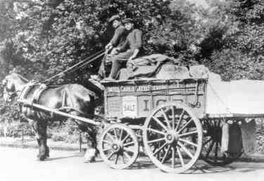 Two men deliver ice and possibly salt to the door, using horse and cart